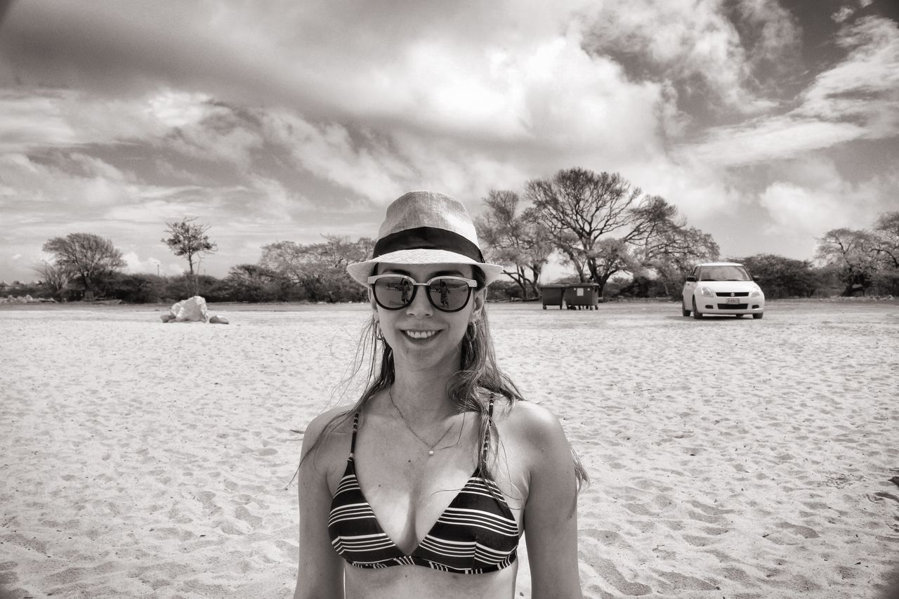 real people, cloud - sky, sky, sunglasses, leisure activity, sand, outdoors, front view, one person, day, beach, looking at camera, lifestyles, vacations, nature, young women, portrait, young adult, standing, tree