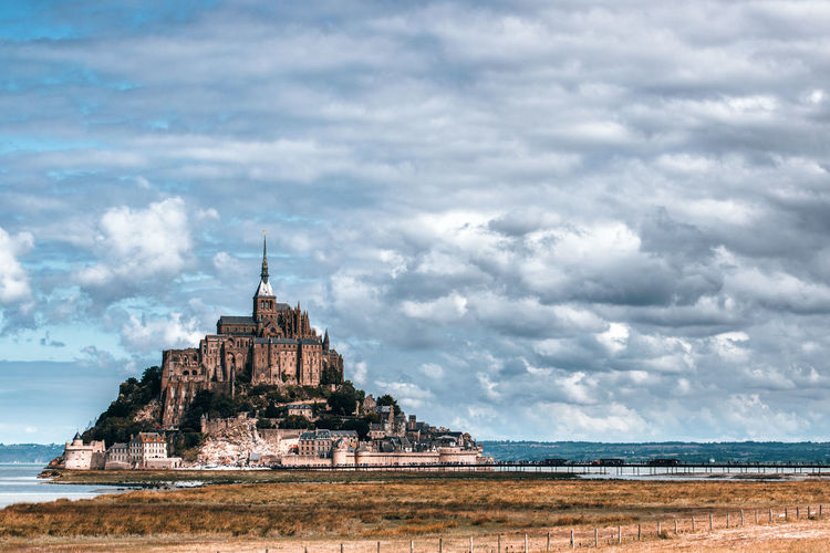 Scenic view of mont saint-michel against cloudy sky