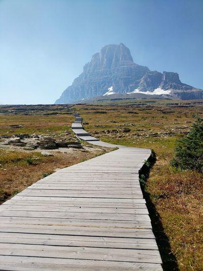 Boardwalk towards mountains against clear sky