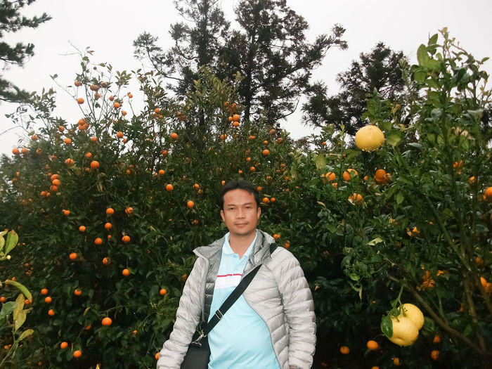 Plant Growth One Person Standing Portrait Looking At Camera Tree Orange Color Nature Real People Young Adult Orange - Fruit Freshness Day Beauty In Nature Food And Drink Fruit Front View Waist Up Fruit Tree Orange Outdoors