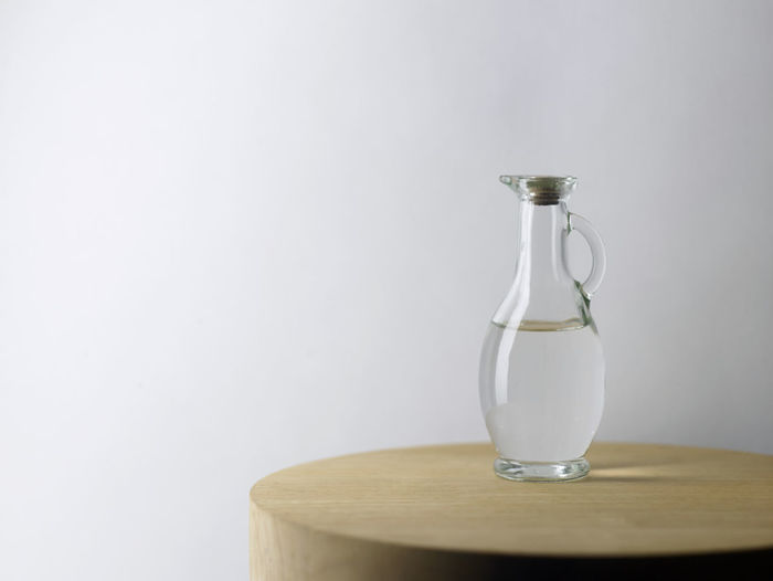 Water in jug on table against white background