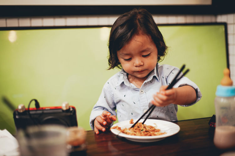 Childhood Child Real People Food And Drink Indoors  Food Kitchen Utensil Front View Table Eating Utensil One Person Innocence Holding Eating Casual Clothing Headshot Cute Lifestyles Sitting