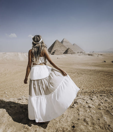 Rear view of woman standing at desert against sky