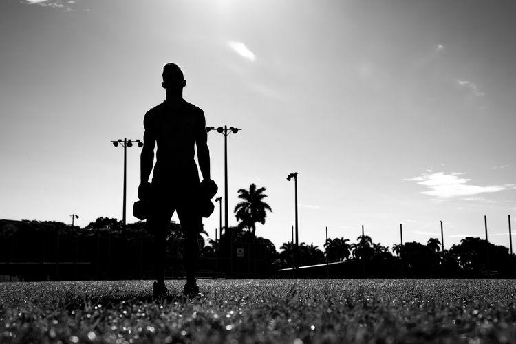 Silhouette men on field against sky