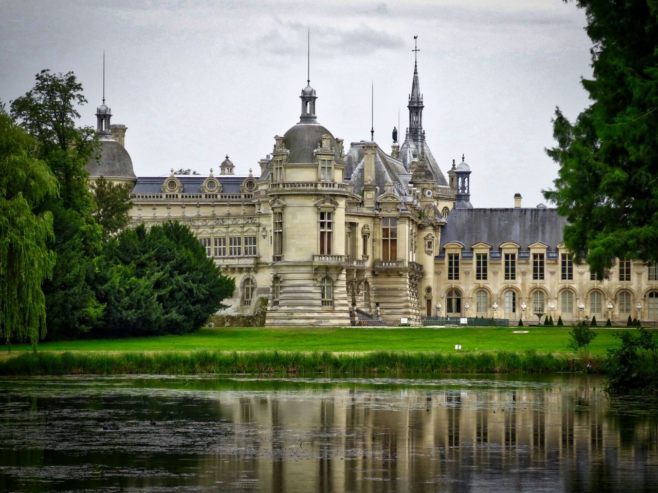 architecture, built structure, water, building exterior, sky, history, travel destinations, reflection, waterfront, outdoors, tourism, day, castle, dome, no people, travel, cloud - sky, place of worship, religion, tree, lake, grass, nature