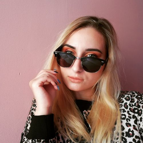 Portrait of young woman wearing sunglasses sitting against wall