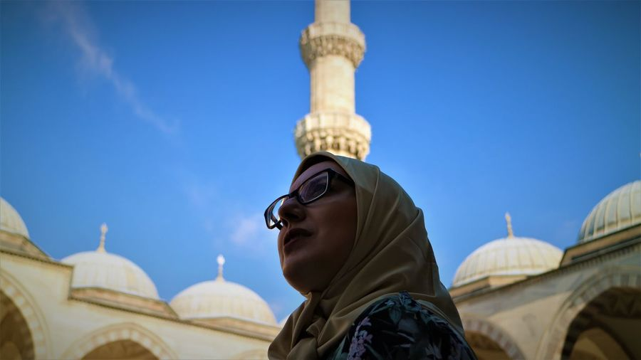 Low angle view of woman at mosque against sky