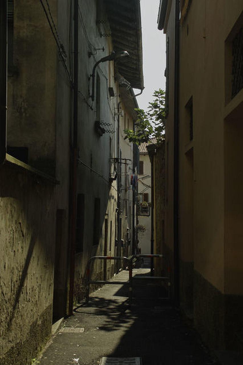 NARROW STREET AMIDST BUILDINGS AGAINST SKY
