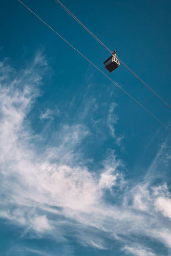 Low Angle View Of Ski Lift Hanging Against Sky