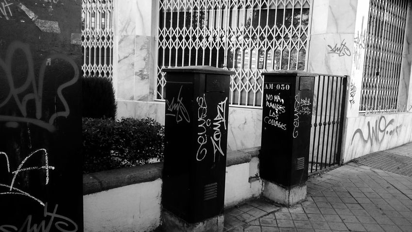 Gate Railing Reflection Architecture Art And Craft Black And White Blackandwhite Building Building Exterior Built Structure City Communication Creativity Day Electricity Meter Footpath Monochrome No People Outdoors Representation Street Street Art Text Wall - Building Feature Western Script