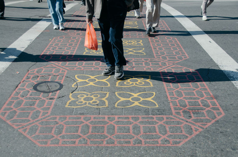 Low section of people walking on floral pattern footpath