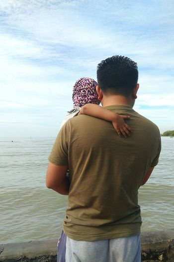 Rear view of man carrying daughter at beach