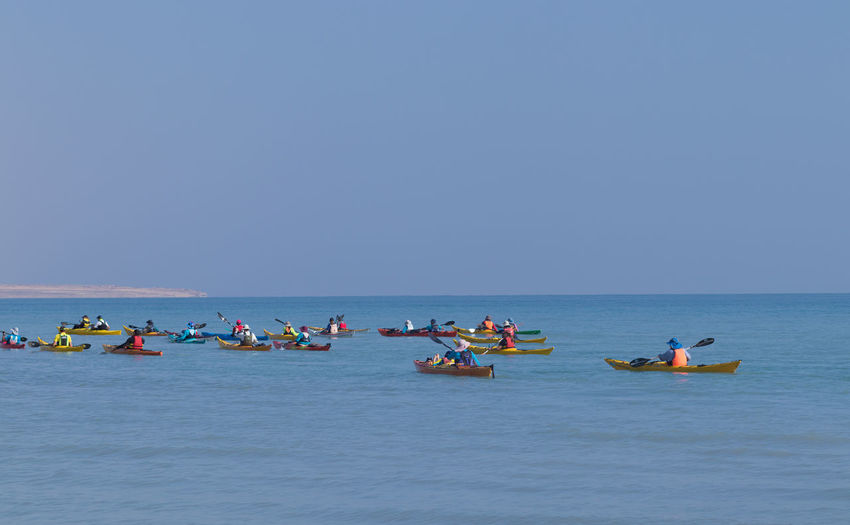 People on boats in sea against clear sky