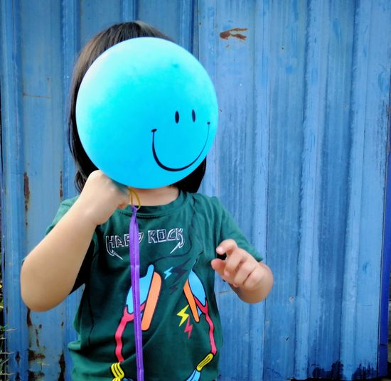 Girl holding balloon while standing against corrugated iron