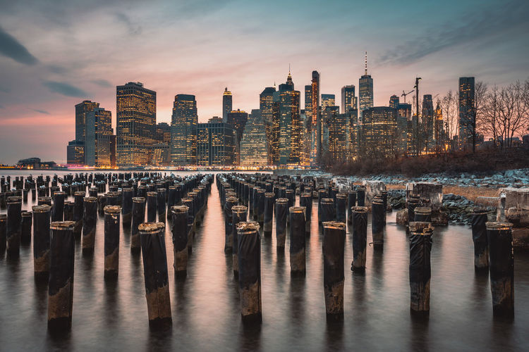 Wooden posts in river against buildings at sunset