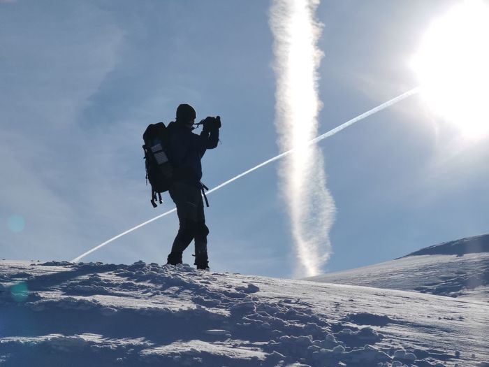 Low angle view of man standing on snow against sky