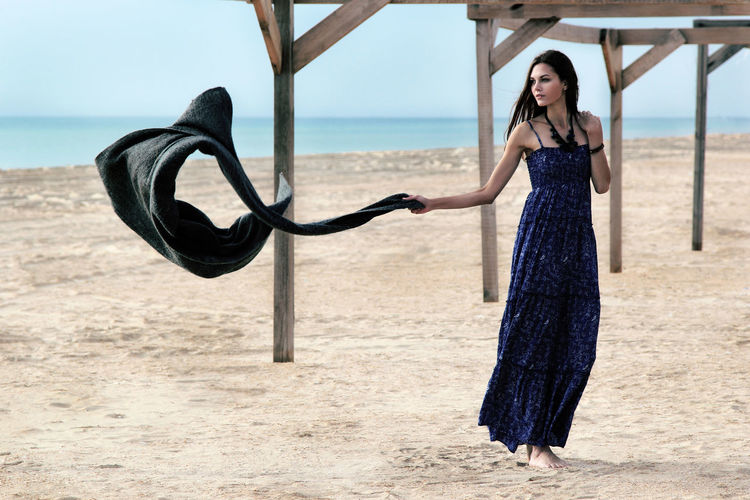 Portrait of a beautiful young woman in a blue dress on a sandy beach. The sea horizon. Sand and blue water. Fashion photo. Photo in motion. Adult Beach Beautiful Woman Beauty Clothing Day Dress Fashion Full Length Hairstyle Land Lifestyles Motion Nature One Person Outdoors Sand Sand & Sea Sandy Beach Sea Standing Wind Women Young Adult Young Women