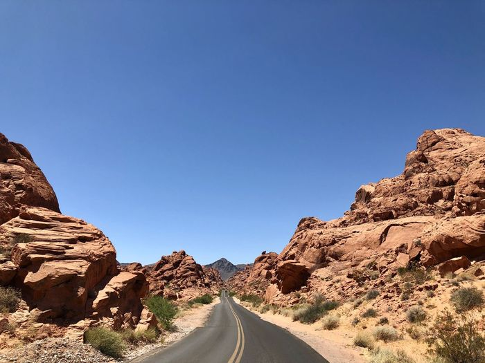 Road amidst rocks against clear blue sky
