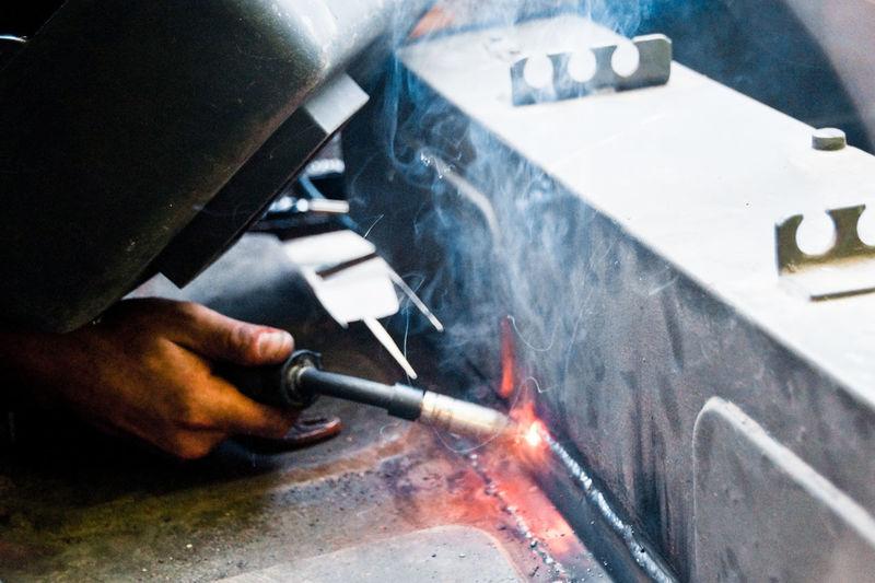 Cropped Hand Of Welder Welding Metal In Factory