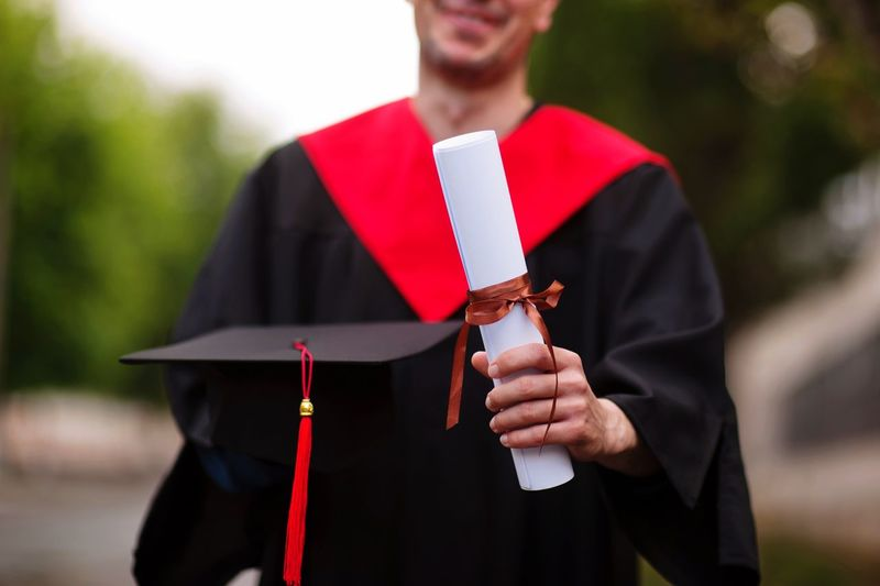 Midsection Of Student Wearing Graduation Gown While Holding Rolled Degree