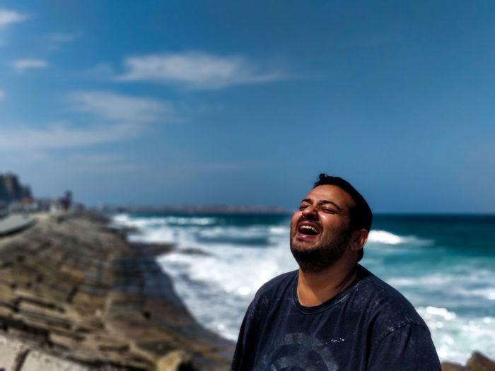 Man laughing while standing against sea and sky