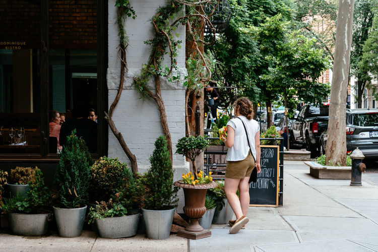 Woman at picturesque in New York Fashion Greenwich NYC NYC Street Tolerance Travel USA West Village Adult America Architecture Bar Building Exterior Built Structure Business Day Fashionable Full Length Greenwich Village Growth Leisure Activity Lifestyles Nature Outdoors People Picturesque Plant Potted Plant Real People Restaurant Retail  Street Travel Destinations Tree Uniform Women