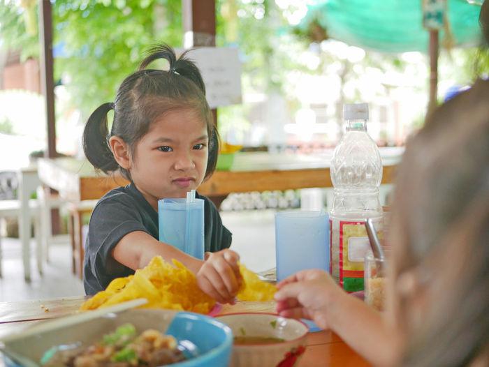 Portrait of boy holding ice cream in restaurant