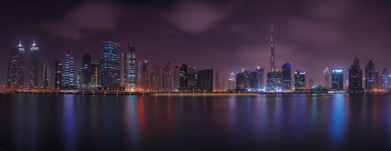 Panoramic view of illuminated city by marina at night