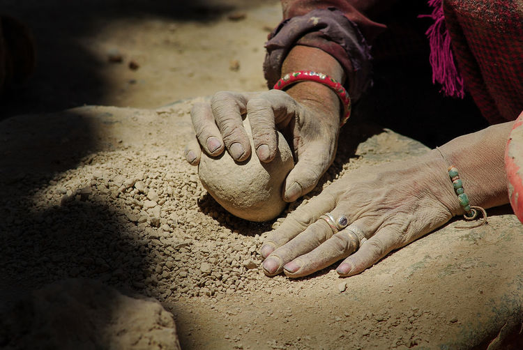 Cropped hands of woman holding rock on land