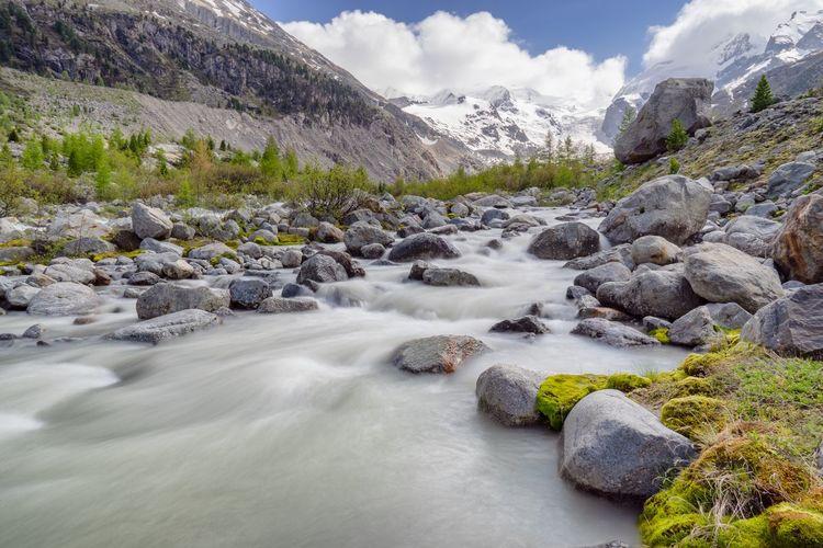 Stream flowing through rocks against sky