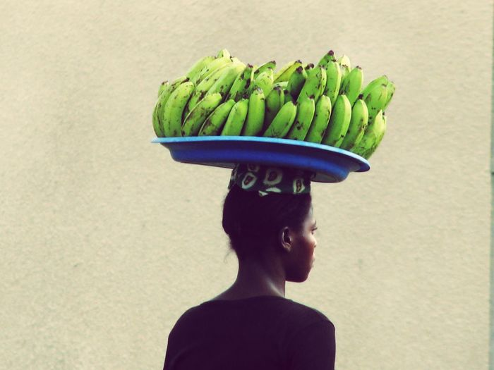 Rear view of man carrying bananas on head against wall