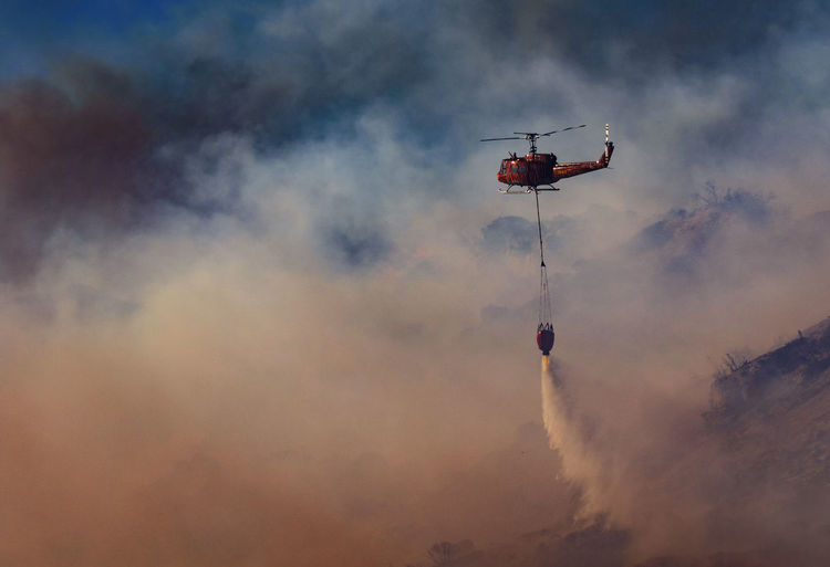 Low angle view of helicopter spraying water against cloudy sky