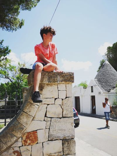 Boy Looking Away While Sitting On Stone Wall Against Sky