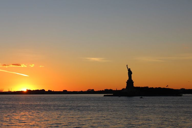 Silhouette Statue Of Liberty By Sea Against Sky During Sunset