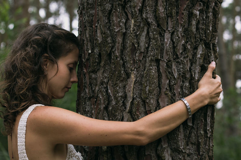 Side view of woman hugging tree trunk