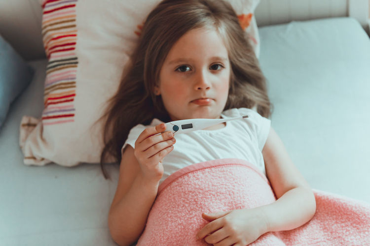 Portrait of girl holding thermometer while lying on bed