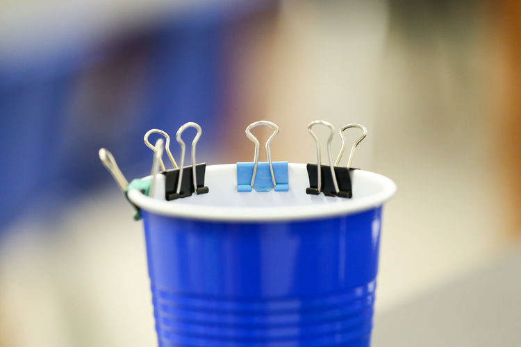 Binder clips on a blue drink cup Office Attached Binder Clips Blue Close-up Container Drink Focus On Foreground Group Household Equipment Inline Lined Up Little Metal No People Office Supplies Paperclips Plastic Recycling Selective Focus Solo Cup