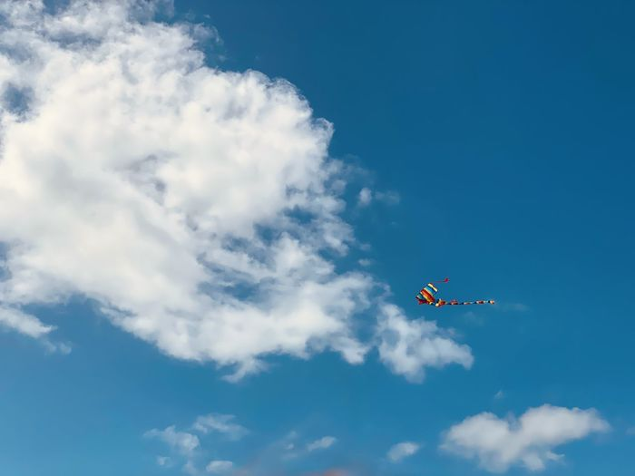 Low angle view of a kite flying against blue sky