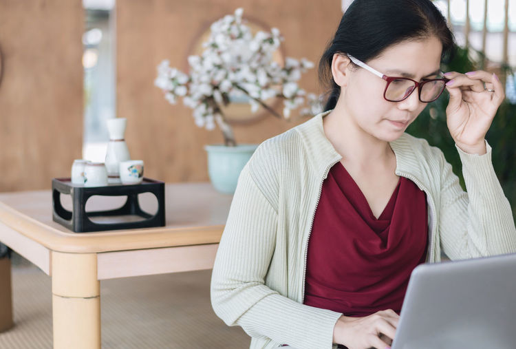 Woman use laptop : Lifestyles Laptop Computer Technology Wireless Technology Woman Eyeglasses  Working Work At Home Domestic Room Domestic Life Sitting Adult One Person Cardigan