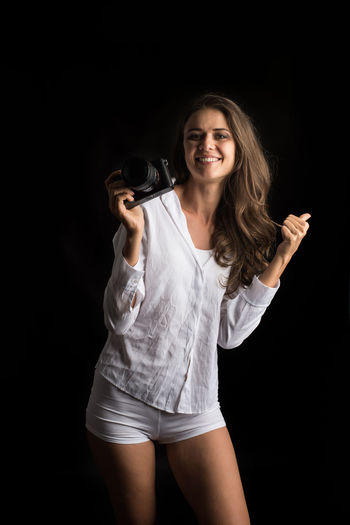 Portrait Black Background Looking At Camera Smiling Studio Shot Young Adult One Person Three Quarter Length Happiness Hair Standing Front View Beautiful Woman Adult Hairstyle Young Women Indoors  Technology Holding Casual Clothing