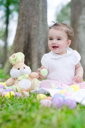 Cheerful Baby Girl With Toys Sitting On Field