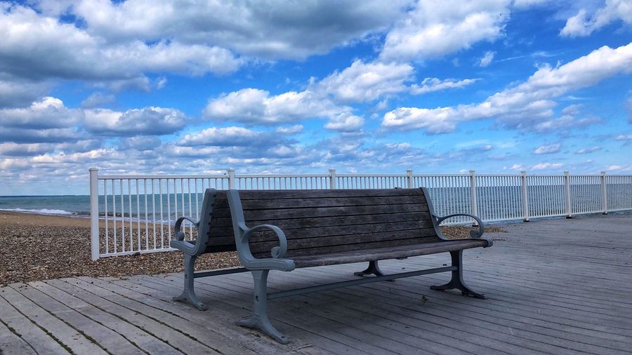 Back to back benches by the water Cloud - Sky Sky Sea Beach Water Nature Land Scenics - Nature Beauty In Nature Tranquility Day Tranquil Scene No People Seat Sand Protection Security Wood - Material Outdoors Horizon Over Water