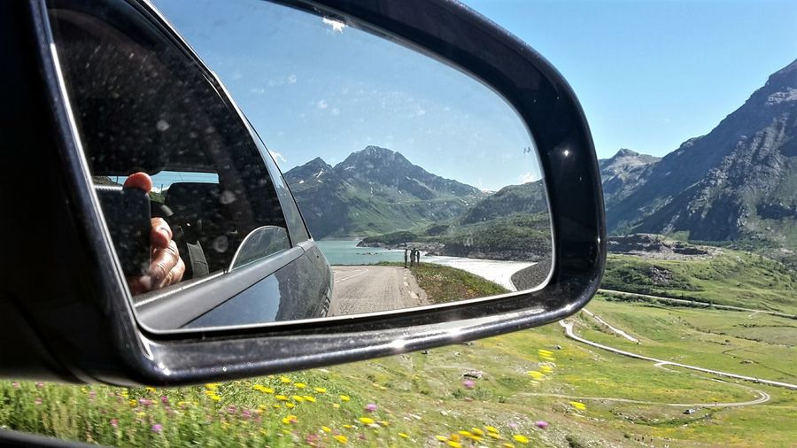 Mountain reflecting in side-view mirror of car