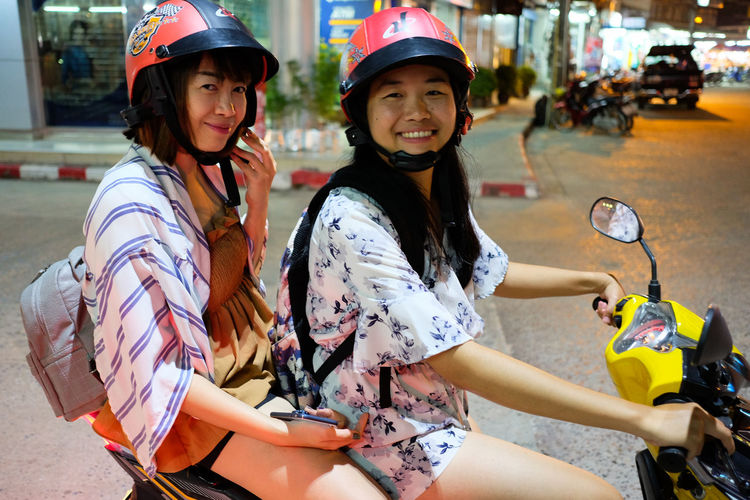 Portrait of smiling women on scooter in city