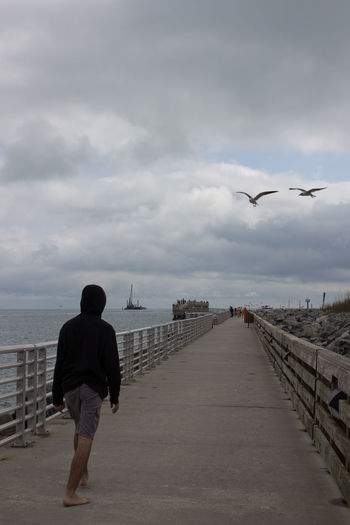 Walking the pier Bare Foot Bird Cloud - Sky Flying Full Length Horizon Over Water Inle Lake Jetty Park One Person Outdoors Pier Rear View Sea Seagulls Seagulls In Flight Travel Destinations Young Man