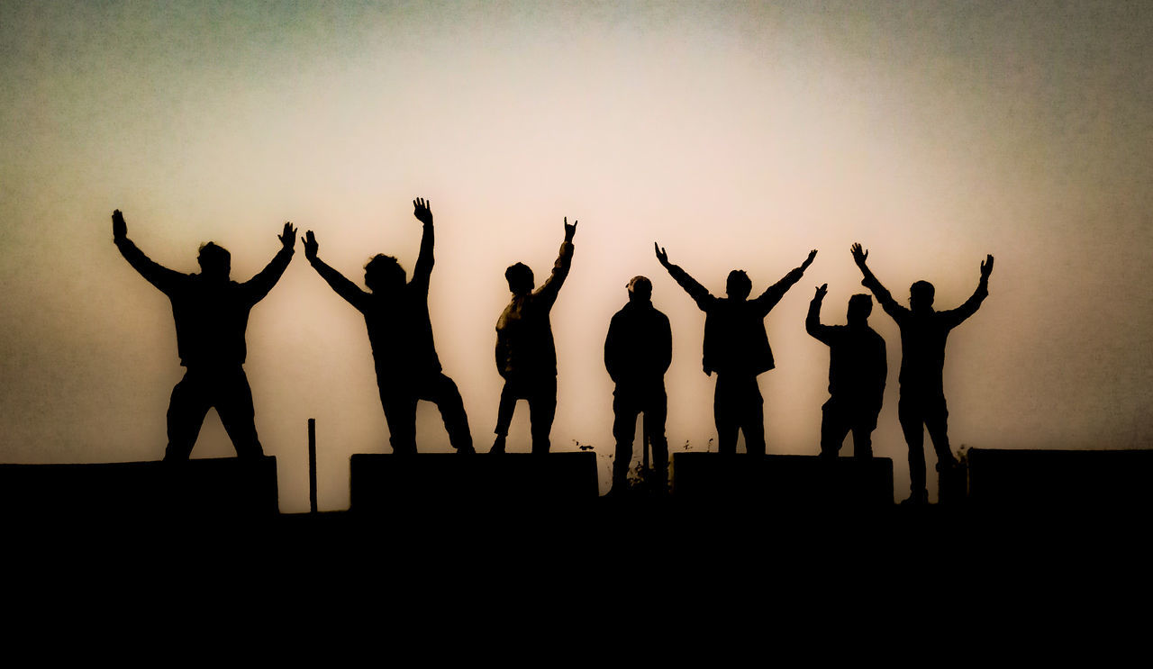 SILHOUETTE PEOPLE STANDING AGAINST SKY WITH ARMS RAISED