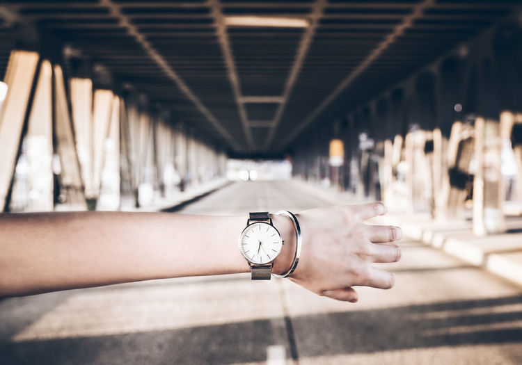 Midsection of person with clock on bridge