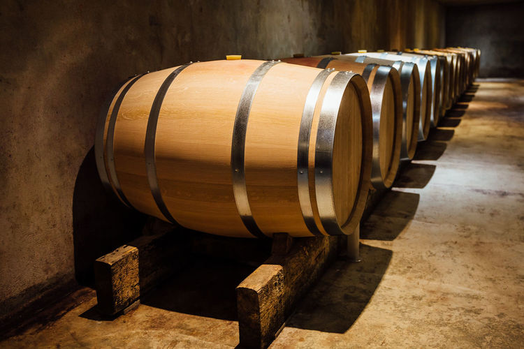 Wine maturing in oak barrels in a cellar. Barrel Cellar Wine Cask Wine Cellar Cylinder Wood - Material Wine Food And Drink Winemaking Indoors  In A Row Alcohol Drink Refreshment Winery Food And Drink Industry Ageing Maturing Aligned Cask Oak Row Storage