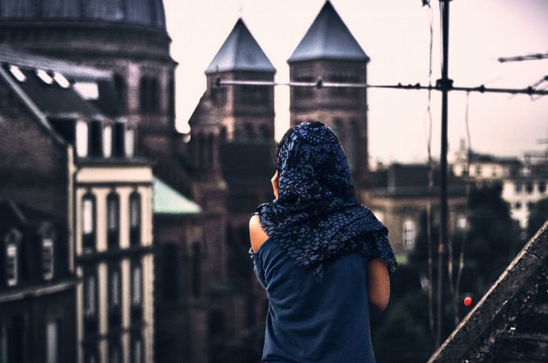 Rear view of woman looking at church in city