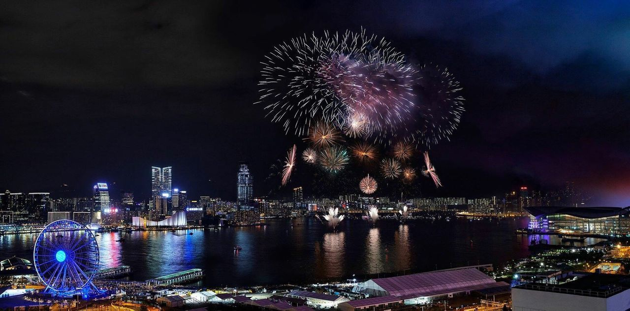 FIREWORK DISPLAY OVER RIVER BY BUILDINGS AGAINST SKY